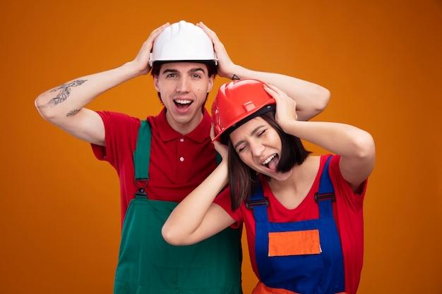 Jong koppel vrolijke man benadrukt meisje in bouwvakker uniform en veiligheidshelm houden handen op hoofd man kijken camera meisje schreeuwen met gesloten ogen geïsoleerd op oranje muur
