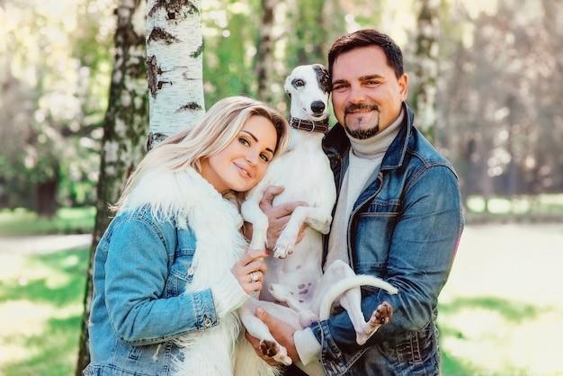 Jong koppel vrouw en man in denim kleding wandelen met twee whippet honden buiten in de herfst
