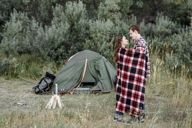 Jong koppel wandelaars man en vrouw staat in de buurt van tent en kampvuur in de natuur