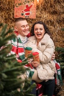 Jong koppel wandelen in de kersttuin bij de kerstboom