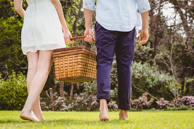 Jong koppel wandelen in de tuin met picknickmand