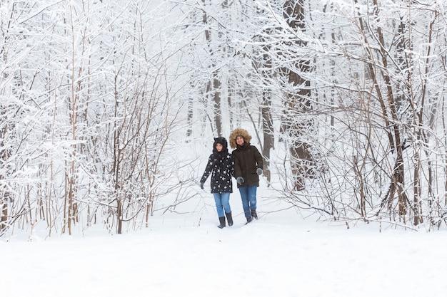Jong koppel wandelen in een besneeuwd park. winter seizoen.