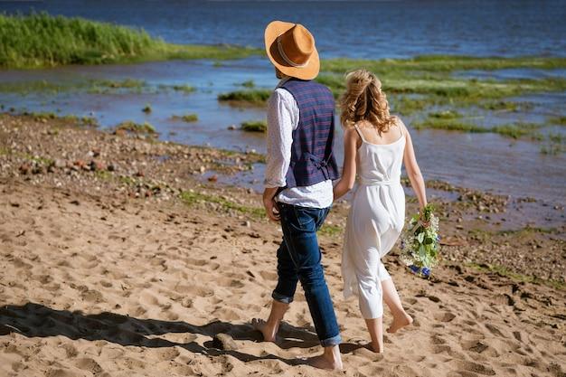 Jong koppel wandelen langs het strand op een zonnige zomerdag