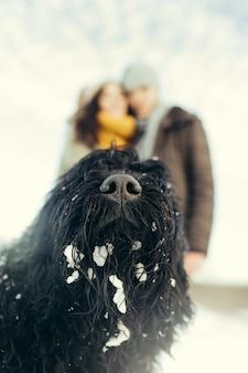 Jong koppel wandelen met een hond in een winterse dag