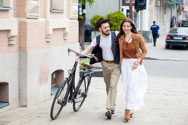 Jong koppel wandelen met fiets en knuffelen