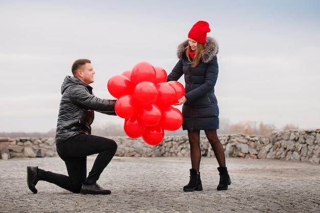 Jong koppel wandelen met rode ballonnen