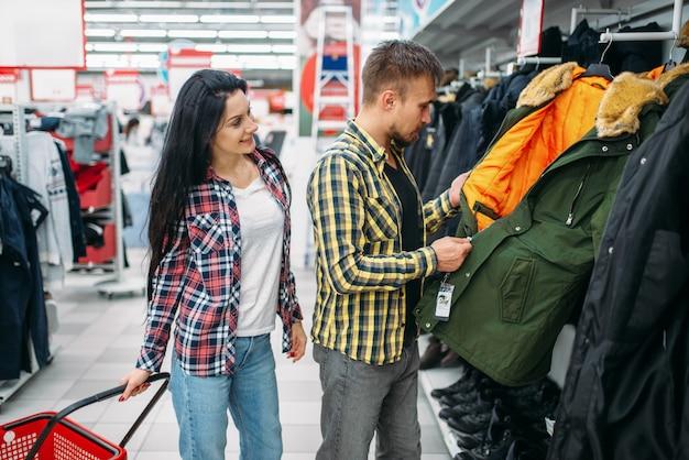 Jong koppel warme kleren kiezen in de supermarkt