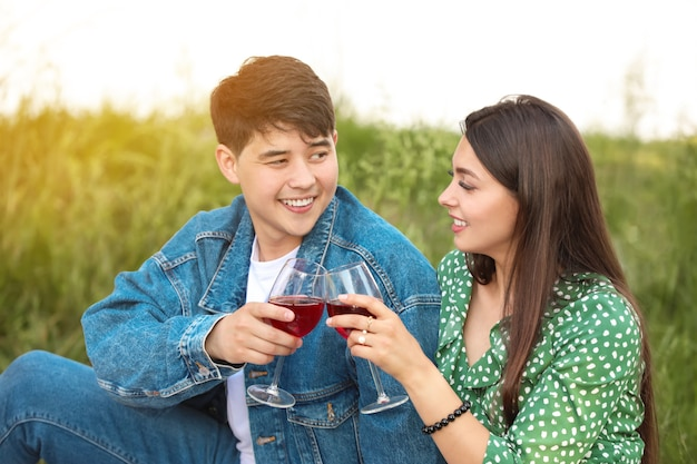 Jong koppel wijn drinken op picknick in park