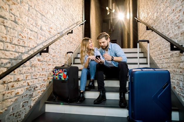 Jong koppel zakenmensen reizigers, met koffers, zittend op de trap en met behulp van mobiele telefoon