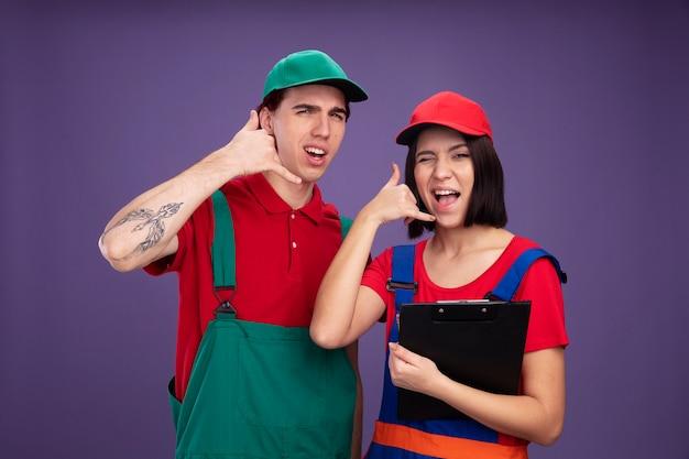 Jong koppel zelfverzekerde man en vrolijk meisje in bouwvakkeruniform en pet doet oproepgebaar meisje met potlood en klembord knipogen