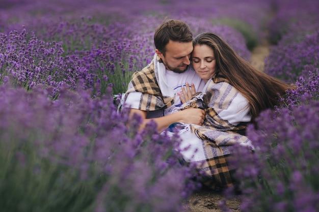 Jong koppel zitten en knuffelen samen op het lavendelveld op zomerdag