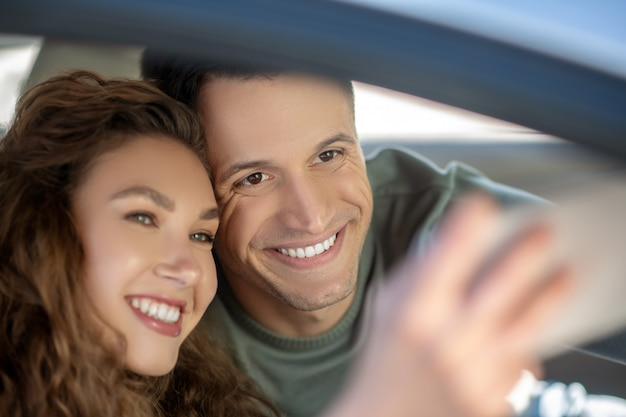 Jong koppel zitten in de auto en het maken van selfie