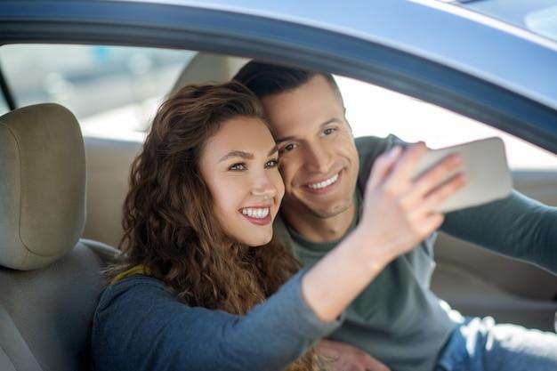 Jong koppel zitten in de auto, selfie maken en glimlachen