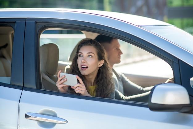 Jong koppel zitten in de auto, vrouw foto's maken en op zoek verrast