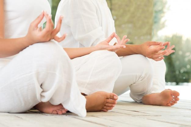 Jong koppel zitten in een lotus houding en mediteren