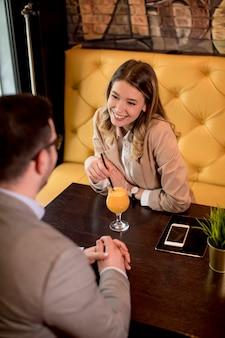 Jong koppel zitten in het café en het drinken van jus d'orange