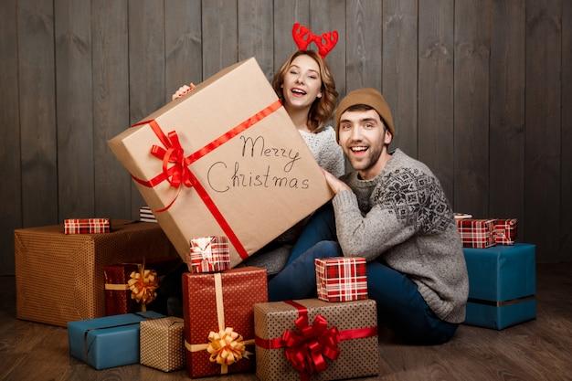 Jong koppel zitten onder kerst geschenkdozen over houten muur