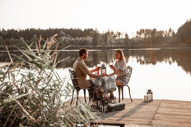 Jong koppel zittend aan tafel tijd samen doorbrengen op houten pier op bosmeer verjaardag vieren, hand in hand. liefde hangt in de lucht, liefdesverhaalconcept. romantische date op meer met kaarsen.