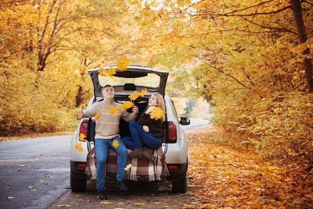Jong koppel zittend in de kofferbak van een auto op de weg in de herfst