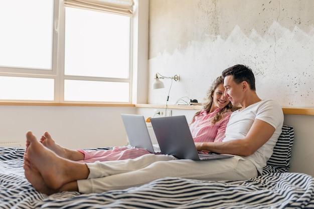 Jong koppel zittend op bed in de ochtend, man en vrouw die op laptop werkt