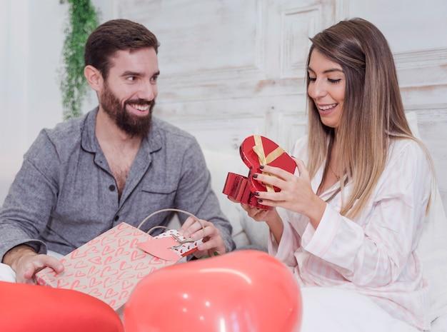 Jong koppel zittend op bed met geschenken