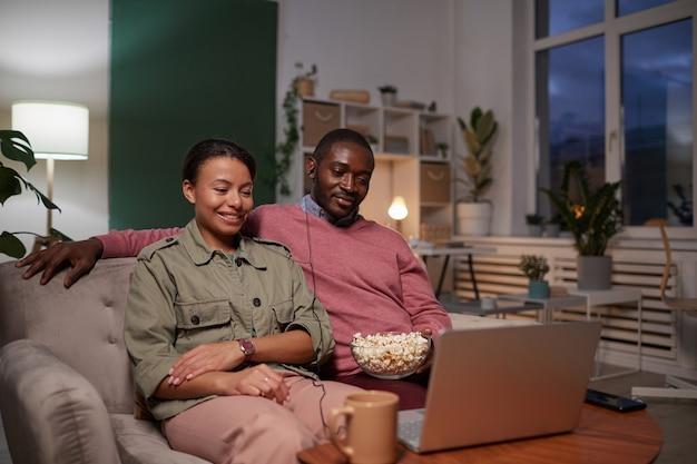 Jong koppel zittend op de bank met popcorn en kijken naar een interessante film op laptop thuis