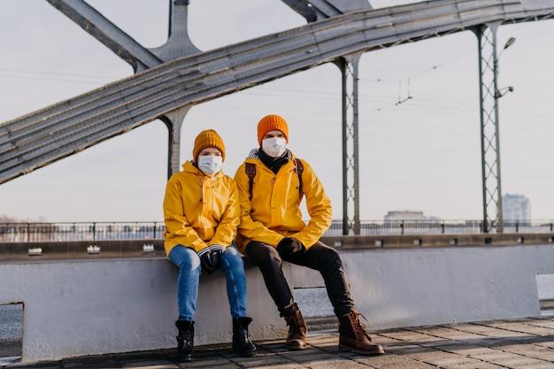 Jong koppel zittend op de brug in beschermende gezichtsmaskers, gekleed in gele windjacks, na te denken over hun problemen veroorzaakt door pandemie van coronavirus. gezondheidszorg concept.