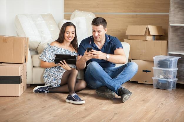 Jong koppel zittend op de vloer. jong koppel zittend op de vloer met behulp van tablet pc na verhuizing naar hun nieuwe huis