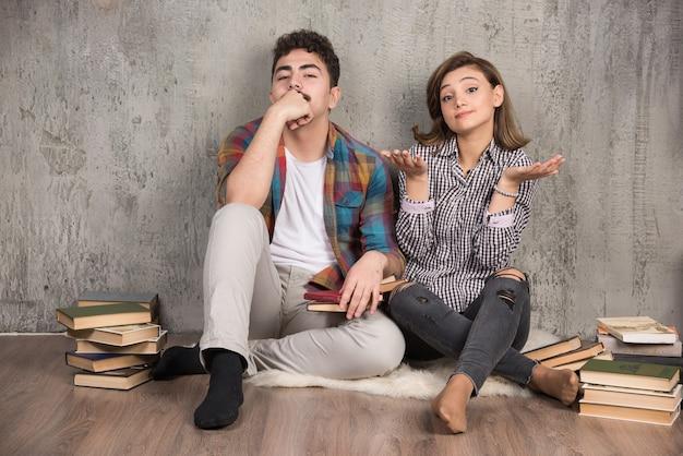 Jong koppel zittend op de vloer met boeken en denken