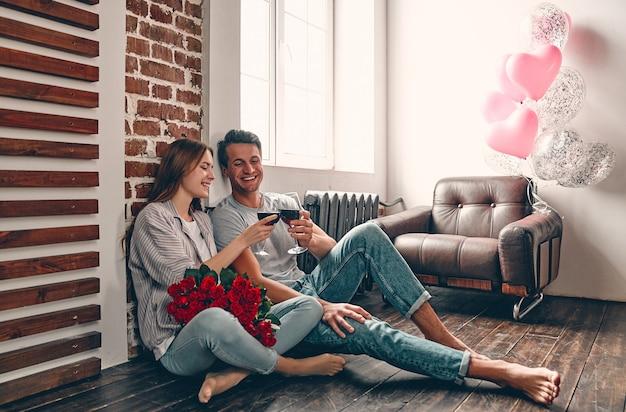 Jong koppel zittend op de vloer met glazen wijn en rode rozen