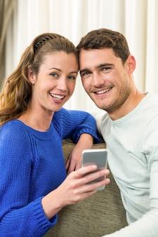 Jong koppel zittend op een bank en het gebruik van mobiele telefoon in de woonkamer