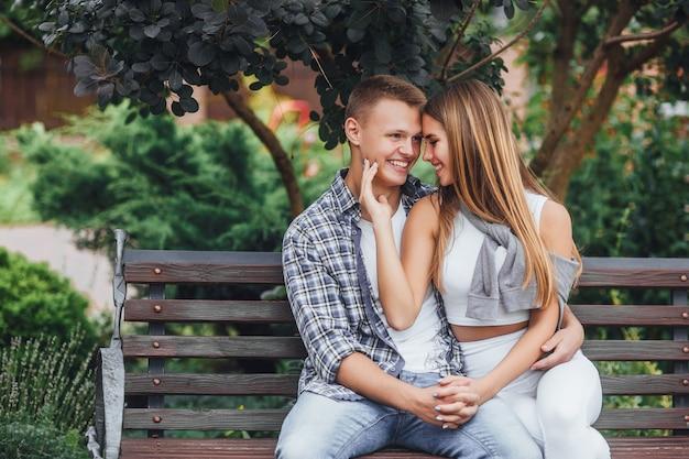 Jong koppel zittend op een bankje in het park en glimlachen. een man die een meisje knuffelt en er recht uitziet.