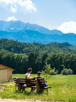 Jong koppel zittend op een houten bankje op een groene met gras begroeide heuvel, genietend van het panoramische uitzicht op de alpen