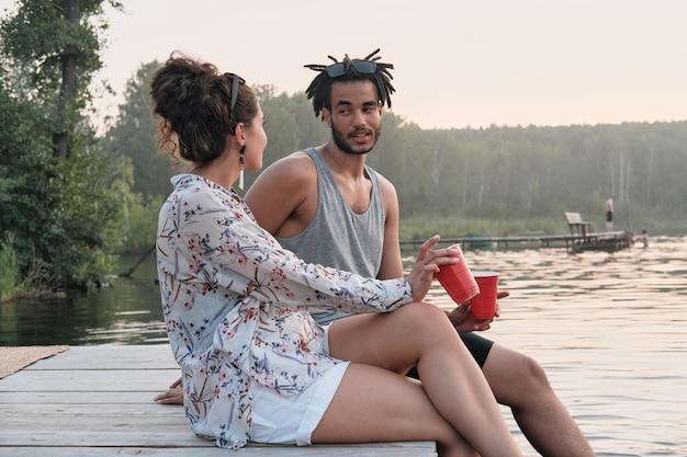Jong koppel zittend op een pier met cocktails en met elkaar praten tijdens zomerdag