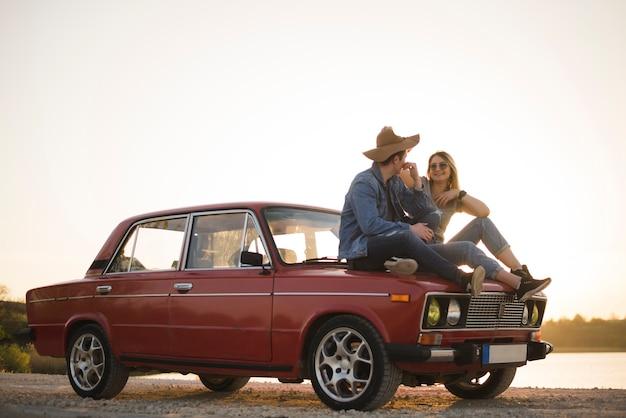 Jong koppel zittend op een vintage auto