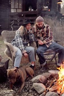 Jong koppel zittend op fauteuils samen met hond en kijkend naar vuur genieten ze van de tijd in de frisse lucht buiten