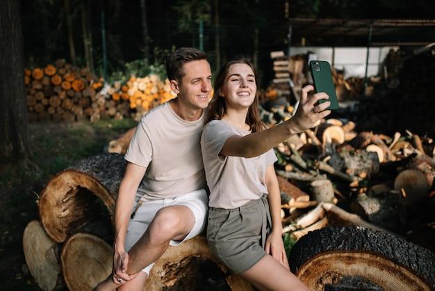 Jong koppel zittend op gekapte bomen in het bos, selfies nemend op hun mobiele telefoons
