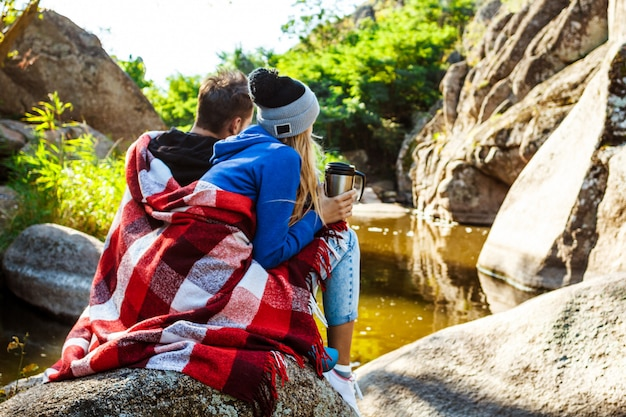 Jong koppel zittend op rots in canyon, het drinken van thee