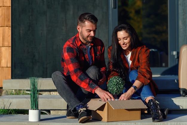 Jong koppel zittend op trappen plezier dozen uitpakken na verhuizing naar een nieuw huis.