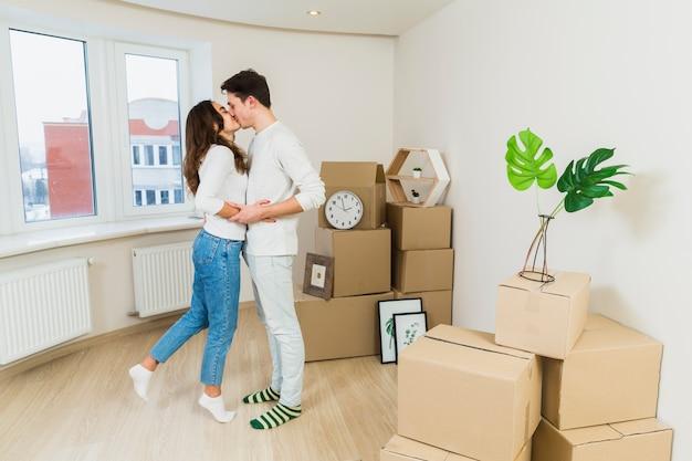 Jong koppel zoenen elkaar met kartonnen dozen in hun nieuwe huis