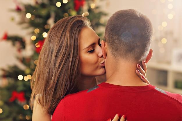 Jong koppel zoenen over kerstboom christmas
