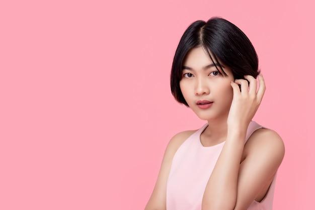Jong kort haar aziatische vrouwenmodel die roze mouwloze blouse dragen