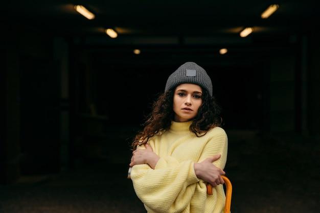 Jong krullend meisje in gele trui en grijze pet blijven alleen bij de stadslichten en bevriezen