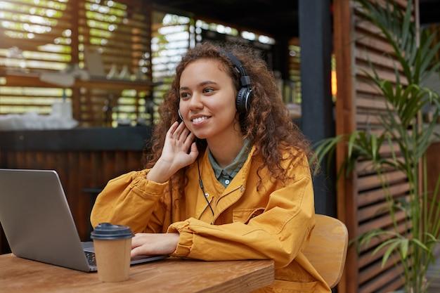 Jong krullend studentenmeisje met donkere huid, zittend op een caféterras, gekleed in een gele jas, met laptop, glimlacht breed en geniet van de favoriete muziek.