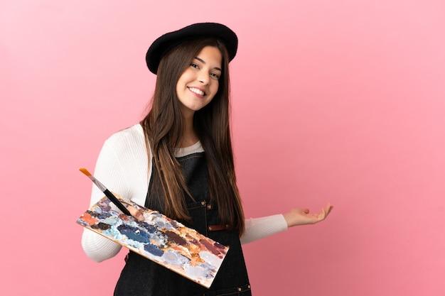 Jong kunstenaarsmeisje dat een geïsoleerd palet houdt en handen naar de zijkant uitstrekt om uit te nodigen om te komen
