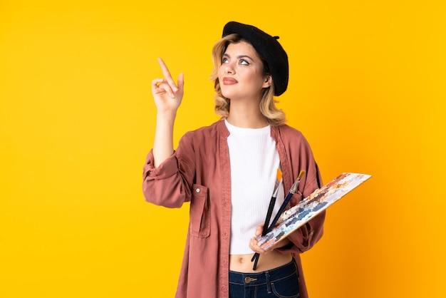 Jong kunstenaarsmeisje dat een palet houdt dat op gele muur wordt geïsoleerd en met de wijsvinger een geweldig idee richt