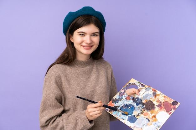 Jong kunstenaarsmeisje dat een palet over purpere muur houdt