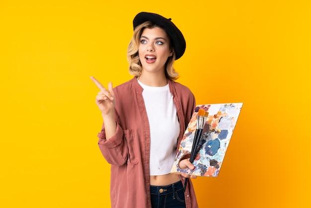 Jong kunstenaarsmeisje die een palet houden dat op gele muur wordt geïsoleerd verrast en wijzende vinger naar de kant