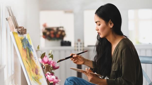 Jong kunstenaarsmeisje die een verfborstel houden en olieverf trekken op canvas