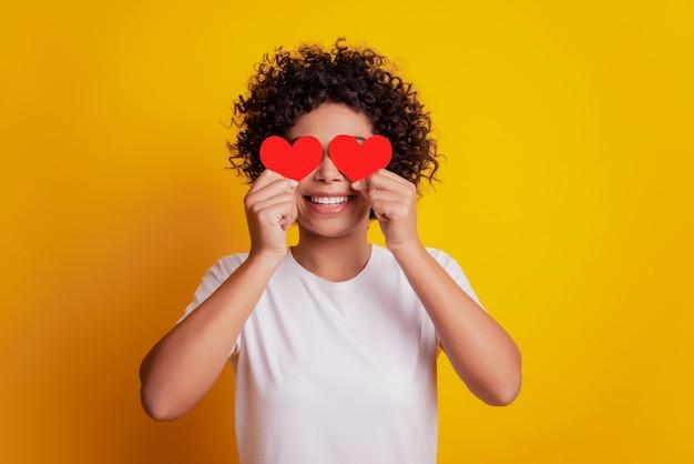 Jong lachend afrikaans meisje houdt twee kleine papieren hartfiguren vast, bedek de ogen en draag een wit t-shirt op een gele muur